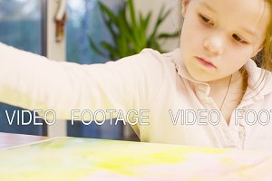 Young artist painting on paper with