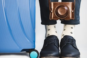 Stylish suitcase, men's legs