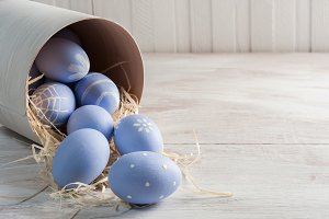Painted eggs on white wooden boards