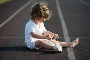 girl learning to tie shoelaces