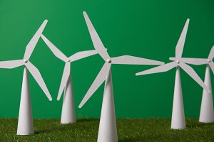 white windmill models on grass and g