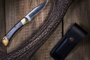 Classic hunting knife on a wooden.