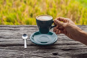 A man's hand holds a cup of coffee