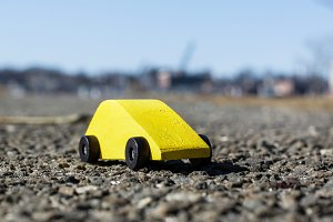Yellow wooden toy car on asphalt