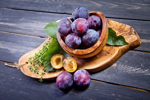 Plums on wooden table close-up. Heal