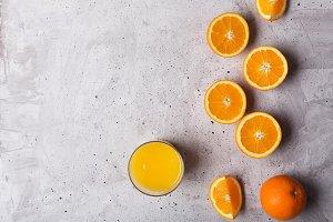 Glass of orange juice on the gray ba