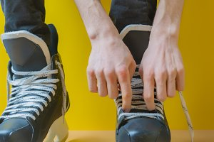 person tying shoelaces on a skates b