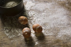 Eggs and flour on a sieve with a wooden background.