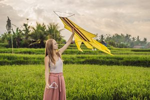 Young woman launches a kite in a
