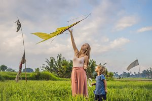 Mom and son launch a kite in a rice