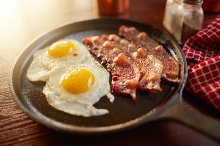 fried bacon and eggs in iron skillet
