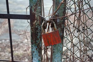 Rusty metal gate closed with padlock
