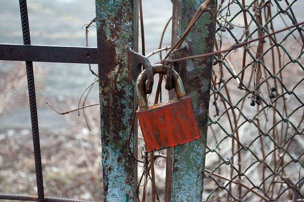 Stock Photos: musicphoto - Rusty metal gate closed with padlock