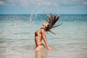 Beautiful woman jumps out of the sea