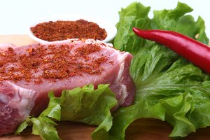 Raw pork steak with herbs, chili