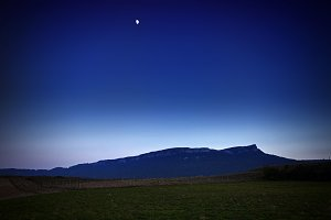 Mountain silhouette and moon at nigh