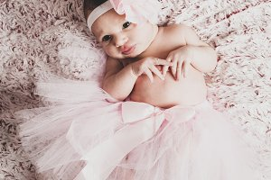 Newborn baby girl wearing a pink bal