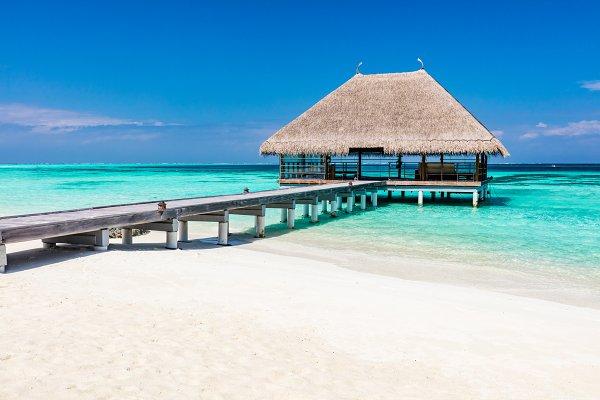 Wooden jetty on blue ocean in Maldi…