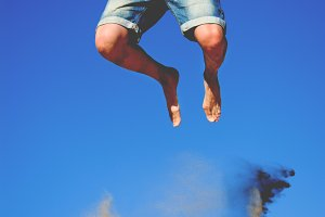 young man jumping on a dune