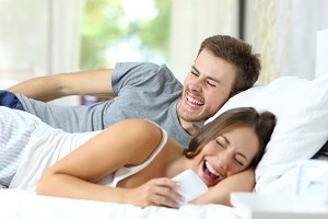 Couple on bed laughing watching phon