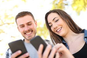 Happy couple using their smart phone