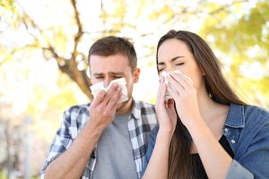 Sick couple sneezing together in a p