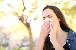 Sick woman sneezing covering nose in