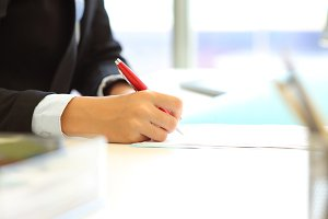 Office worker hand signing contract