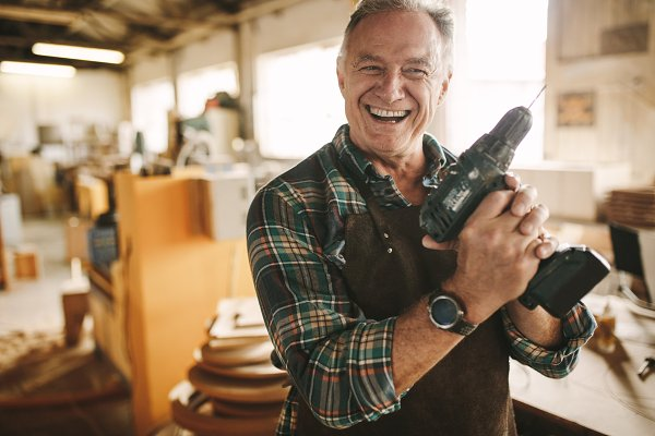 Smiling senior carpenter holding