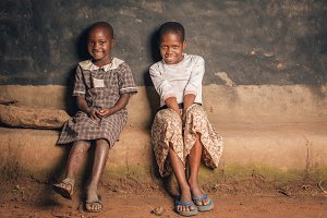 Two African Girls Sit & Smile at Hut