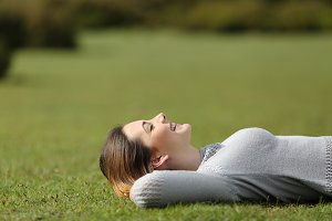Beautiful woman resting on the grass in a park.jpg