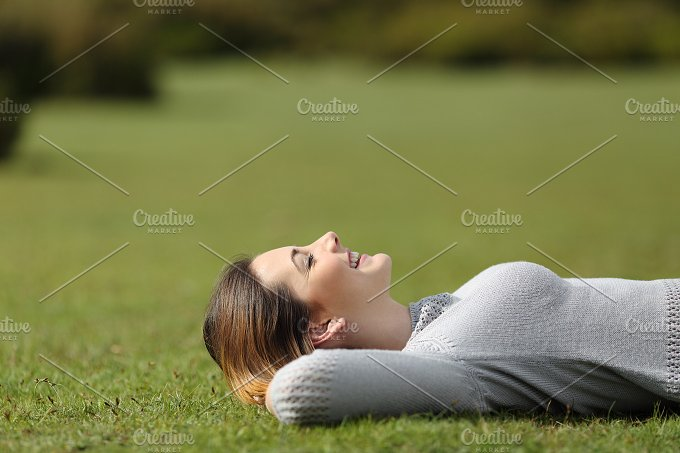 Beautiful woman resting on the grass in a park.jpg - Health