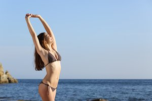 Beautiful fitness woman body wearing a swimsuit on the beach.jpg