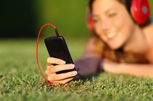 Close up of a woman with headphones holding a smart phone.jpg
