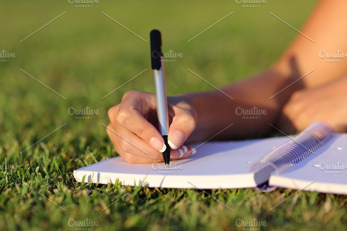 Close up of a woman hand writing on a notebook outdoor.jpg - Education