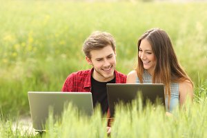 Couple or friends watching laptops in a field.jpg