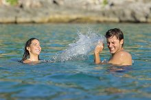 Couple playing bathing on the beach in summer vacation.jpg