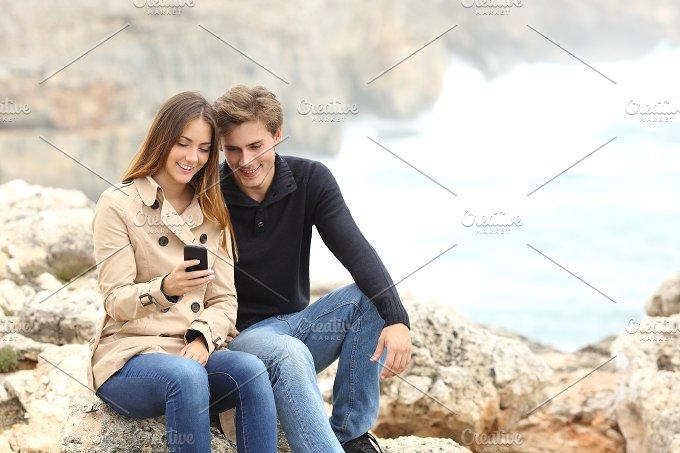 Couple sharing a smart phone on the beach on holidays.jpg - Technology