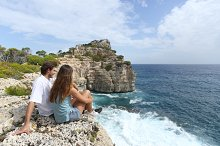 Couple sitting in a cliff watching ocean landscape.jpg