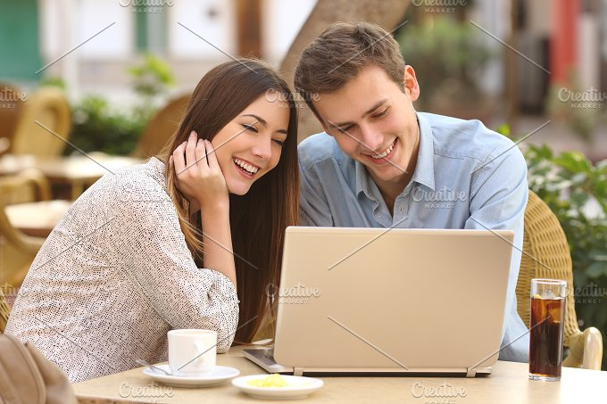 Couple watching media in a laptop in a restaurant.jpg - Technology