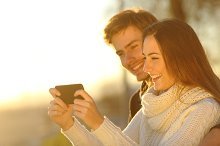 Couple watching media videos in a smart phone.jpg
