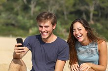 Funny man and woman laughing watching the smart phone.jpg