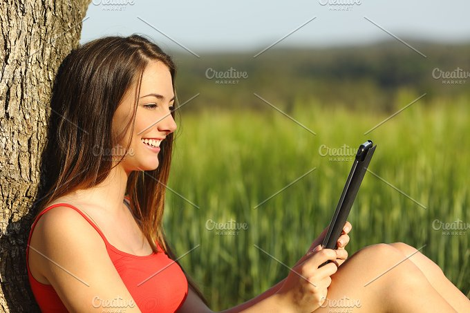 Girl reading an ebook or tablet in a green field.jpg - Technology