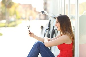 Girl sitting using a mobile phone in a park.jpg