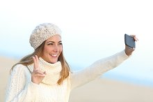 Girl taking a selfie with her smart phone in winter.jpg