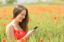 Girl texting in a smart phone in a colorful field.jpg