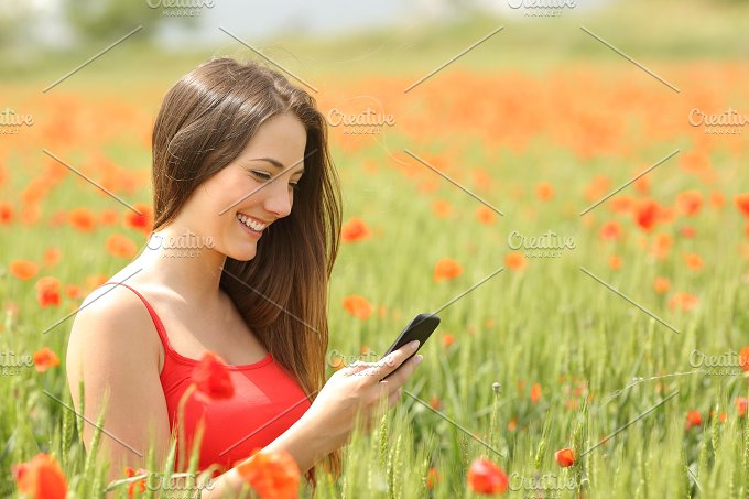 Girl texting in a smart phone in a colorful field.jpg - Technology