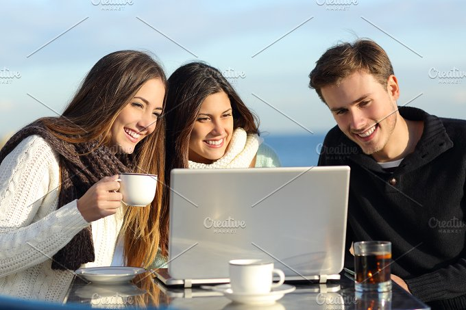 Group of friends watching a laptop in a restaurant.jpg - Technology