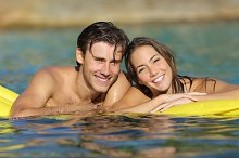Happy couple bathing on the beach in summer vacation.jpg