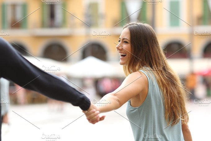 Happy tourist woman laughing and pulling her boyfriend .jpg - People